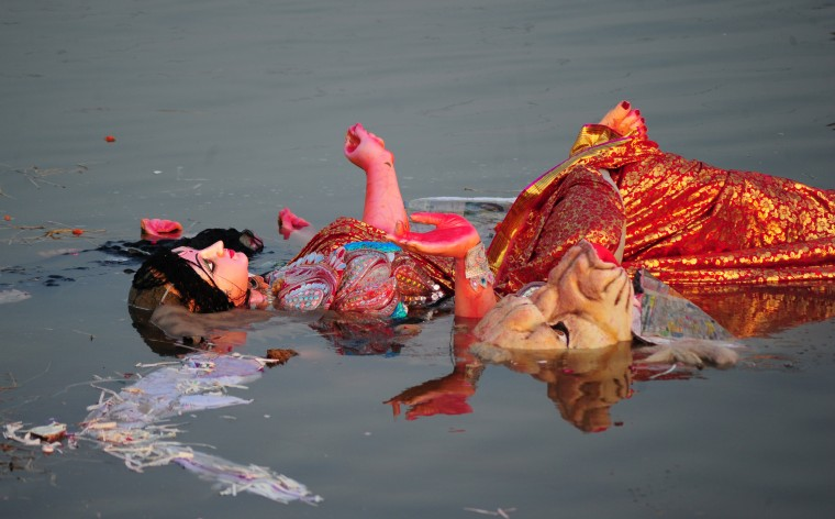 An idol of the Hindu goddess Durga floats in a temporary pond near Sangam after immersion in Allahabad. The Durga Puja festival commemorates the slaying of a demon king Mahishasur by goddess Durga, marking the triumph of good over evil. (Sanjay Kanojia/AFP-Getty Images)