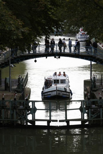 People use a footbridge to cross over the Canal Saint-Martin on a warm autumn afternoon in Paris October 11, 2014. Inauguarated in 1825, the 4.5 km waterway comprised of nine locks runs through the 10th and 11th districts of the French capital. (John Schults/Reuters)