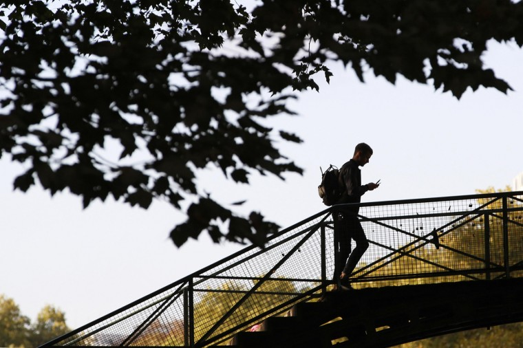A man crosses a footbridge over the Canal Saint-Martin on a warm autumn afternoon in Paris October 11, 2014. Inauguarated in 1825, the 4.5 km waterway comprised of nine locks runs through the 10th and 11th districts of the French capital. (John Schults/Reuters)
