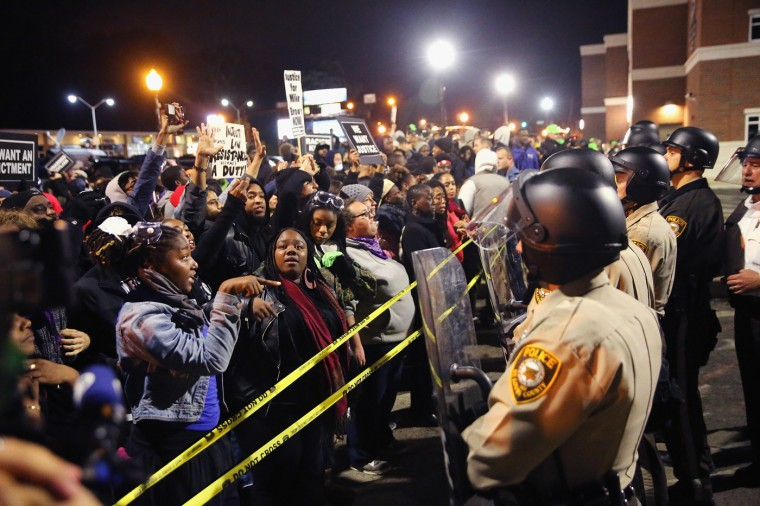 Demonstrators protest outside the Ferguson police department on October 11, 2014 in Ferguson, Missouri. Ferguson has been plagued with protests which have sometimes turned violent since the death of 18-year-old Michael Brown who was shot and killed by Darren Wilson, a Ferguson police officer, on August 9. (Photo by Scott Olson/Getty Images)