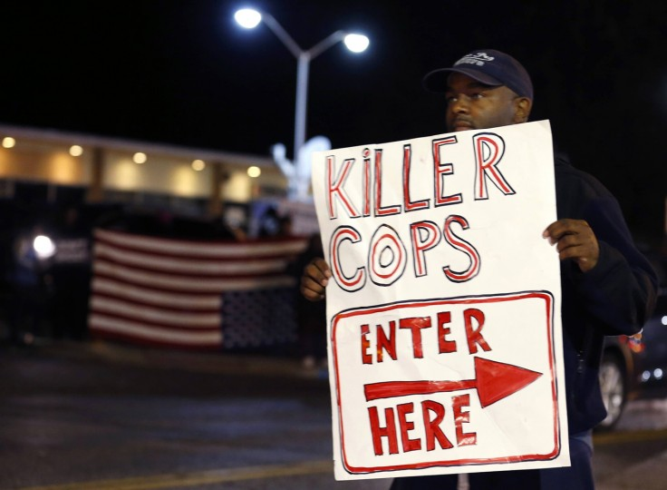 A protester holds up a sign on the street across from the police station during a protest in Ferguson, Missouri October 10, 2014. Civil rights organizations and protest groups have invited people from around the country to join vigils and marches from Friday to Monday over the Aug. 9 shooting of Michael Brown. (Jim Young/Reuters)
