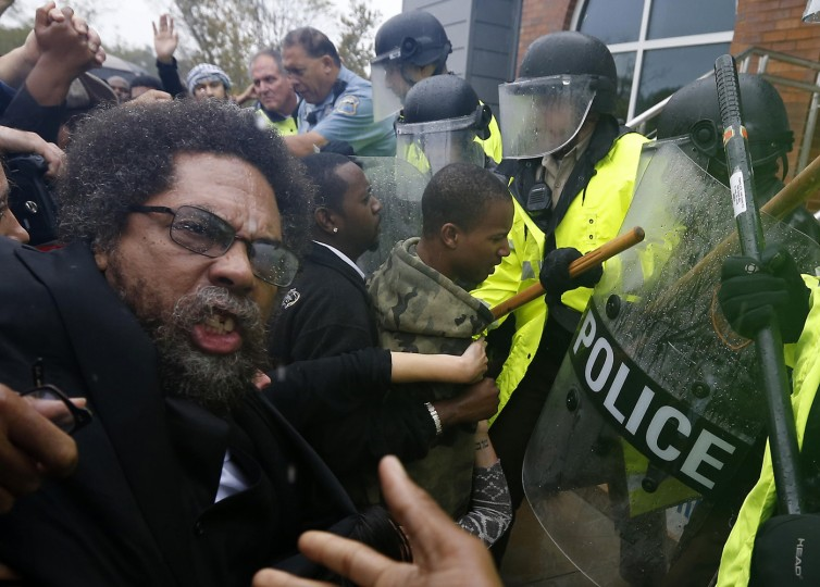 Activist Cornel West is knocked over during a scuffle with police during a protest at the Ferguson Police Department in Ferguson, Missouri, October 13, 2014. Hundreds of protesters converged in the pouring rain on the Ferguson, Missouri, police department on Monday as they launched another day of demonstrations over the August killing by police of an unarmed black teenager. (Jim Young/Reuters)