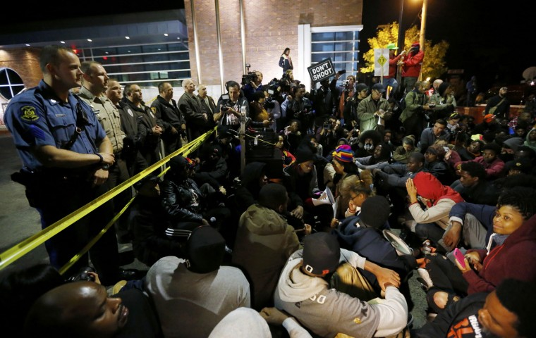 Protesters participate in a sit-in during a rally for Michael Brown outside the police department in Ferguson, Missouri, October 11, 2014. The mother of an unarmed black teenager shot dead by a white officer in Ferguson, Missouri, walked with hundreds of protesters on Saturday in the St. Louis suburb, part of a weekend of protests against police violence. (Jim Young/Reuters)