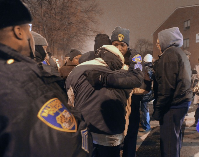 Baltimore City police officers comfort each other as they gather with residents for a candlelight vigil near the corner of Pennsylvania Avenue and Mosher Street for Police Officer William Torbit, who was killed in January 2011. (Kenneth K. Lam/Baltimore Sun)