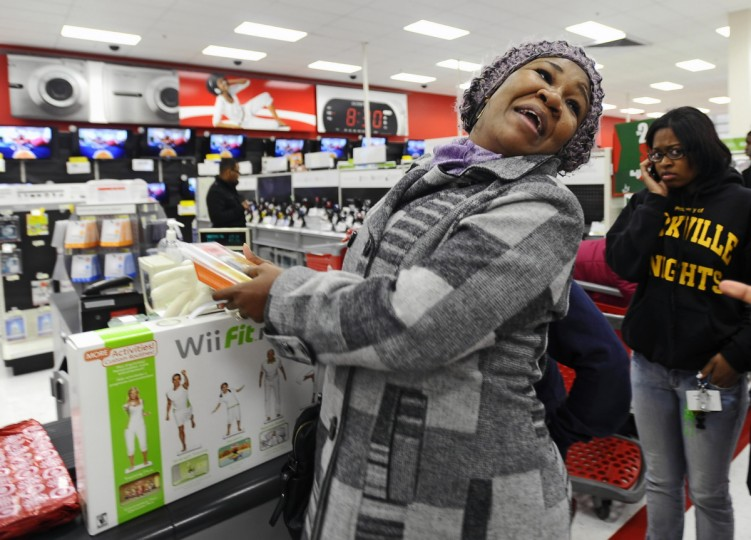 "Shopper Stacy Queen of Baltimore can't seem to contain her joy as she prepares to pay for her of Wii Fit game, GPS system and cell phone at the Target store at Towson Marketplace on ""Black Friday"" in November 2010. (Kenneth K. Lam/Baltimore Sun)"