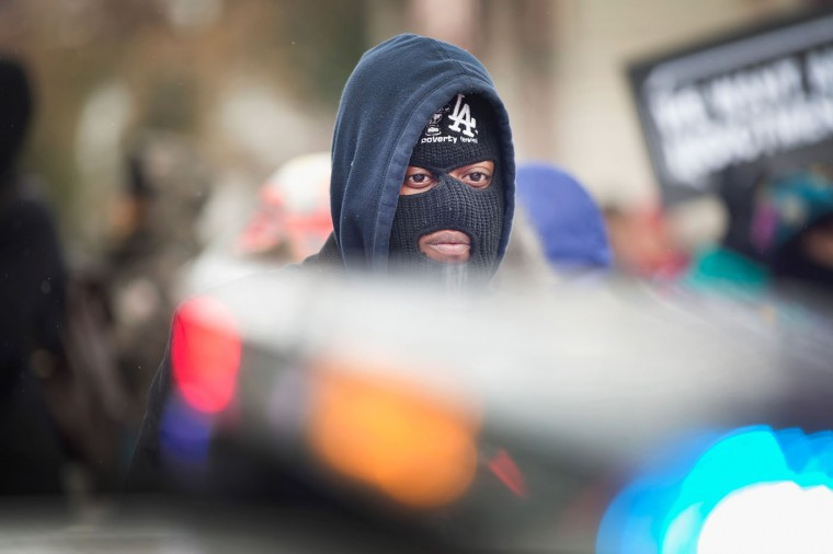 A demonstrator stares down a police officer during a protest marking the 101st day since 18-year-old Michael Brown was killed on November 17, 2014 in Clayton, Missouri. Brown was killed by Darren Wilson, a Ferguson police officer, on August 9. A grand jury in Clayton is sorting through evidence from the shooting to decide if Wilson should be charged in the shooting. The decision is expected sometime this month. (Photo by Scott Olson/Getty Images)