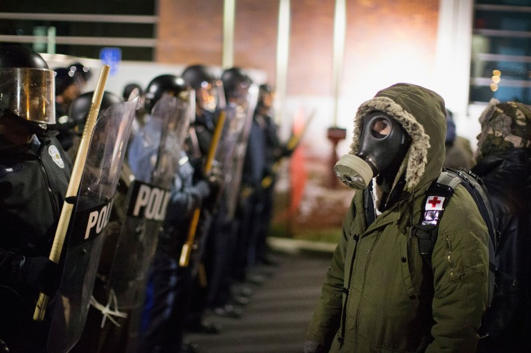 Police confront demonstrators protesting the shooting death of 18-year-old Michael Brown outside the police station on November 19, 2014 in Ferguson, Missouri. Brown was killed by Darren Wilson, a Ferguson police officer, on August 9. A grand jury is expected to decide this month if Wilson should be charged in the shooting. (Photo by Scott Olson/Getty Images)