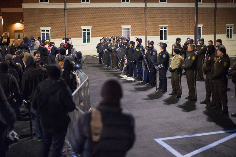 Police confront demonstrators protesting the shooting death of 18-year-old Michael Brown outside the police station on November 20, 2014 in Ferguson, Missouri. At least three people were arrested during the protest. Brown was killed by Darren Wilson, a Ferguson police officer, on August 9. A grand jury is expected to decide this month if Wilson should be charged in the shooting. (Photo by Scott Olson/Getty Images)