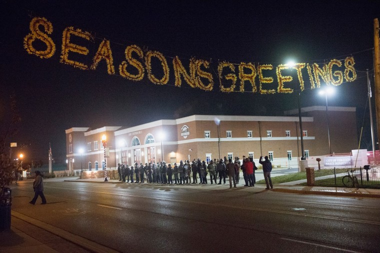 Police guard the police station as demonstrators protest the shooting death of 18-year-old Michael Brown on November 20, 2014 in Ferguson, Missouri. At least three people were arrested during the protest. Brown was killed by Darren Wilson, a Ferguson police officer, on August 9. A grand jury is expected to decide this month if Wilson should be charged in the shooting. (Photo by Scott Olson/Getty Images)