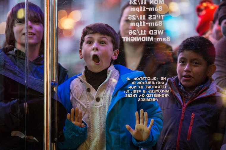 A boy waits to enter the Toys R Us in Times Square on November 27, 2014 in New York, United States. Black Friday sales, which now begin on the Thursday of Thanksgiving, continue to draw shoppers out for deals and sales. (Photo by Andrew Burton/Getty Images)