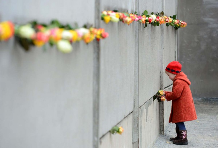 A young girl slips a rose in a preserved segment of the Berlin Wall during the commemorations to mark the 25th anniversary of the fall of the Berlin Wall at the Berlin Wall Memorial in the Bernauer Strasse in Berlin, on November 9, 2014. (John MacDougall/AFP/Getty Images)