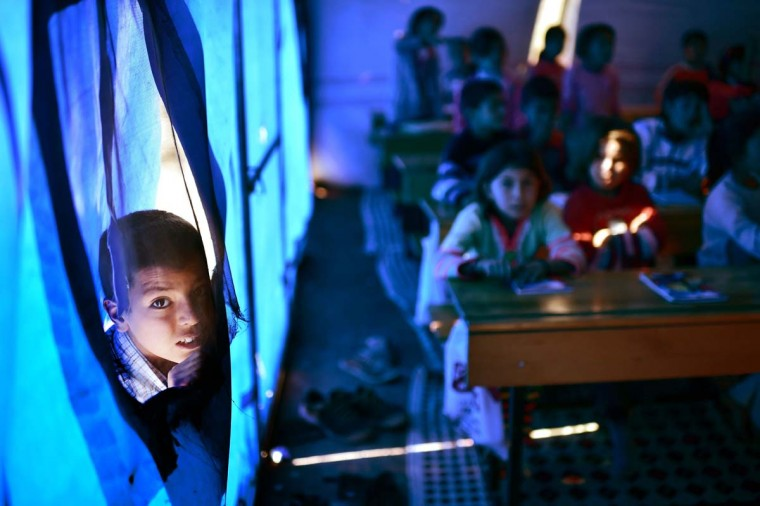 "A Syrian Kurdish boy peers as children take lessons on November 10, 2014 in a makeshift school tent in a refugee camp in the town of Suruc, Sanliurfa province. Turkey's maintained an ""open door"" policy for all those fleeing Syria's civil war and there are now over 1.5 million Syrian refugees living in the country. More than 280,000 Syrian refugees are living in refugee camps, mostly in the southeast, according Turkey's Disaster and Emergency Management Authority (AFAD). (Aris Messini/AFP/Getty Images)"