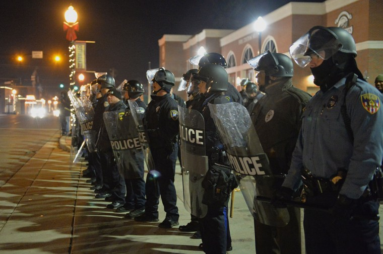 Police officers hold position during a protest on November 20, 2014 outside the Ferguson Police Department in Ferguson, Missouri. The governor of the US State of Missouri declared a state of emergency November 17th and activated the National Guard ahead of a grand jury decision in the case of a black teenager, 18 year-old Michael Brown, shot and killed by a white police officer. Many fear an outbreak of violence if the St. Louis County grand jury fails to indict Ferguson police officer Darren Wilson in the August 9th shooting death. (Michael B. Thomas/AFP/Getty Images)