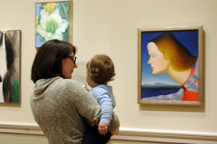 "Kristen Rickard from Baltimore holds her daughter, Lydia, eleven months old, as they look at the artwork in the American Wing. The oil on canvas at right is, ""The Amazon,"" (1925-26)  by the American artist, Joseph Stella. (Algerina Perna/Baltimore Sun)"