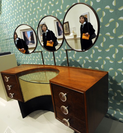 "Kathy Koch from Baltimore is reflected in the mirrors of the vanity designed in 1939 by New York designer Gilbert Rohde. The piece was part of the ""3920 Series"" bedroom furniture series manufactured by Herman Miller, Inc. from Zeeland, Michigan. (Algerina Perna/Baltimore Sun)"