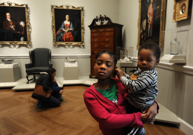 Jordyn Boone, 8, from Baltimore, holds her brother Austyn Boone, 2, as she looks at the paintings and other artwork in the American Wing of the BMA. She came to the museum with her grandmother, Emma Boone, and two more of her siblings (not pictured). (Algerina Perna/Baltimore Sun)