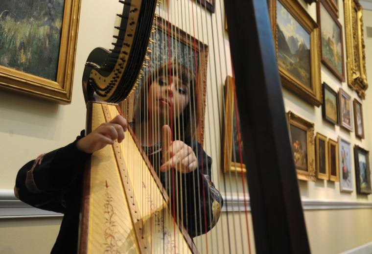Harpist Jasmine Hogan tunes her harp before playing in the Maryland, My Maryland exhibit space of the American Wing. (Algerina Perna/Baltimore Sun)