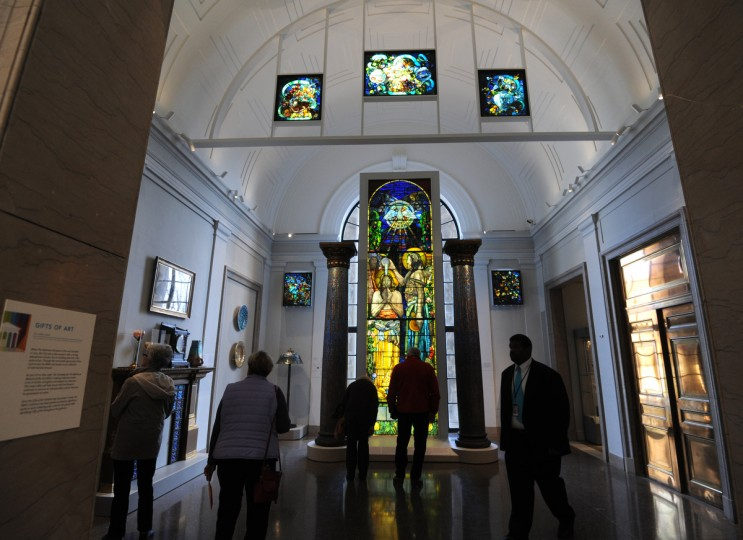 "Visitors look at the Tiffany and Friends display in the American Wing. In the center is the ""Baptism of Christ"" Window, c. 1897, by designer Frank Brangwyn, which was manufactured by Tiffany Glass & Decorating Company, New York. (Algerina Perna/Baltimore Sun)"
