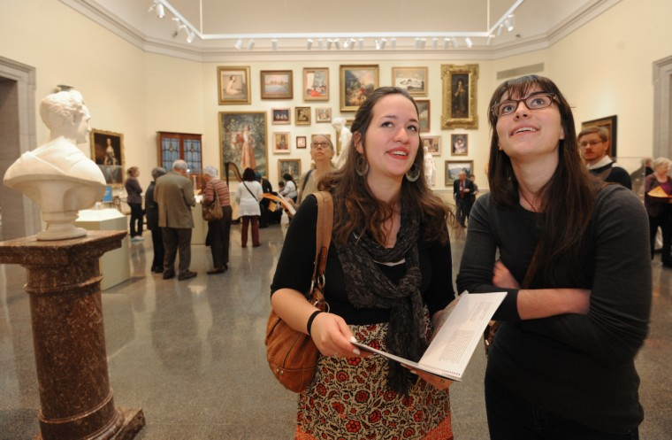 "Michelle Fitzgerald, from Columbia, left, and Emily Huebner from Frederick, who both work for the Maryland State Archives, look at, ""The Thomas Johnson Family, 1772 painting by Charles Willson Peale in the ""Maryland, My Maryland"" exhibit space in the American Wing. (Algerina Perna/Baltimore Sun)"