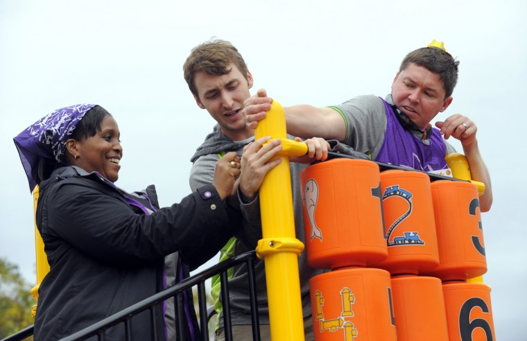 L-R Nicole Cooke, Brann Northcutt and Alex Lenz work together as they volunteer their time to help build the playground. (Lloyd Fox/Baltimore Sun)