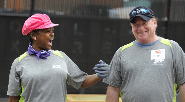 Linda Weaver, left, and Mike Cheek share a laugh while working on the playground. (Lloyd Fox/Baltimore Sun)