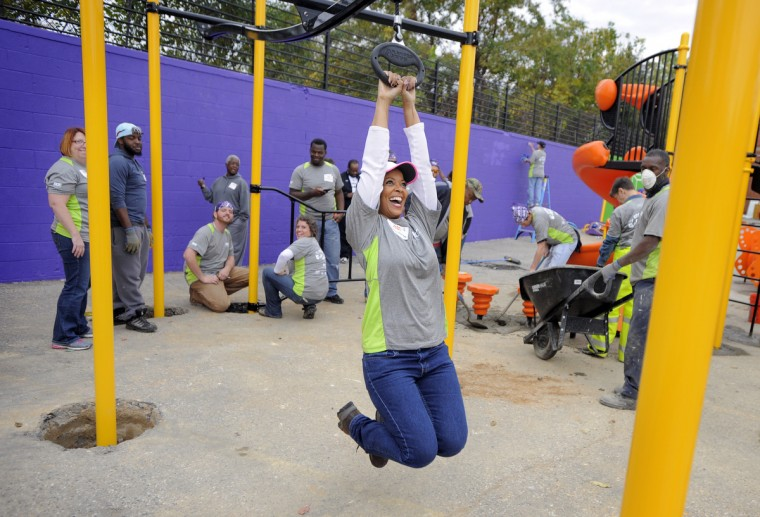Valencia McClure of BGE, takes a test drive on the playground zip line. (Lloyd Fox/Baltimore Sun)