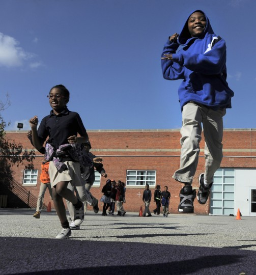 Kyonta Summerville, right, a fourth grader at the school was one of the first on the new playground. (Lloyd Fox/Baltimore Sun)