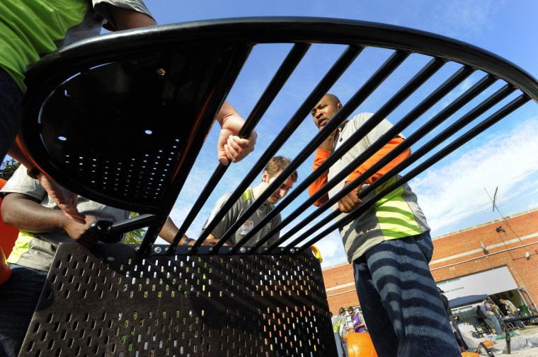 Brann Northcutt, left, and Robert Brooks work on putting together the slide for the playground. (Lloyd Fox/Baltimore Sun)