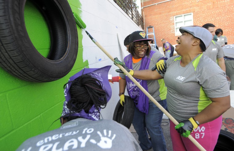 Michele Hughes, center, and Aboladele Oluwafemi, right,  enjoy their time volunteering at the event.  (Lloyd Fox/Baltimore Sun)