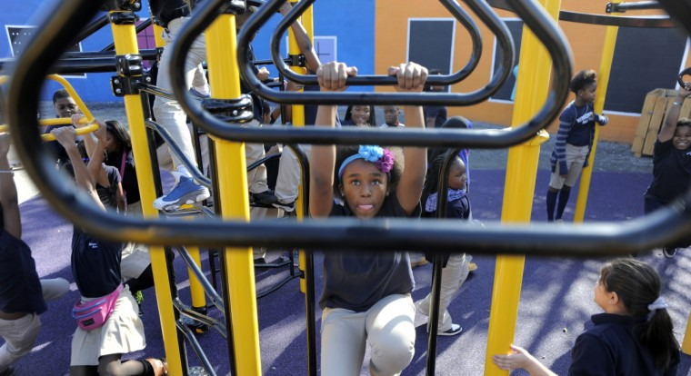 Children from the Monarch Academy Baltimore enjoy the playground equipment built by volunteers recently. (Lloyd Fox/Baltimore Sun)