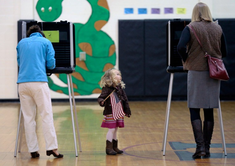 Caroline Tiger, center, watches anothter voter as her mom, Mary Tiger, left, votes in the Perry Harrison Elementary gymnasium near Pittsboro, N.C., on Tuesday, Nov. 4, 2014. Caroline brought her U.S. flag for show and tell at her nearby preschool. Precinct Judge Karen Kolias said the precinct had logged 30 votes in the first 30 minutes of voting. (Harry Lynch/Raleigh News & Observer/MCT)