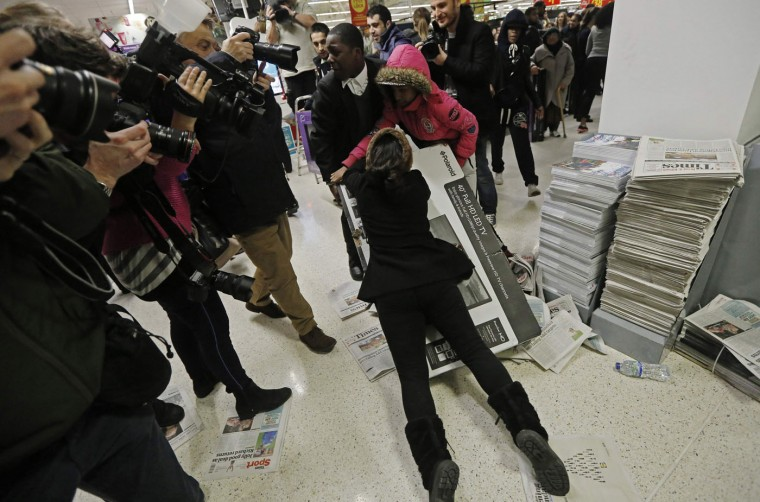 """Shoppers wrestle over a television as they compete to purchase retail items on """"Black Friday"""" at an Asda superstore in Wembley, north London November 28, 2014. Britain's high streets, malls and online sites were awash with discounts on Friday as more retailers than ever embraced U.S.-style """"Black Friday"""" promotions, seeking to kickstart trading in the key Christmas period. In the United States the Friday following the Thanksgiving Day holiday is called Black Friday because spending usually surges and indicates the point at which American retailers begin to turn a profit for the year, or go """"into the black"""". (Luke MacGregor/Reuters)"""