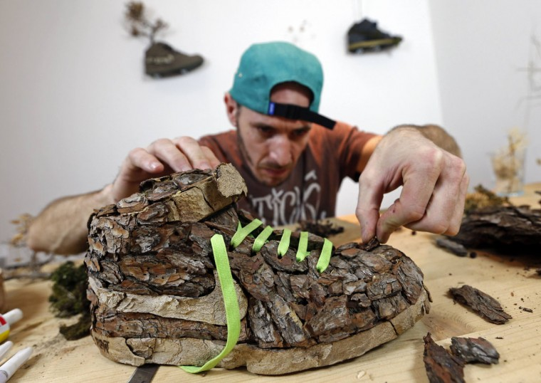 "French artist Christophe Guinet, also known as ""Mr Plant"", works on his plant shoe creation ""Wood "", part of the artistic project ""Just Grow It"", in his art gallery in Marseille, November 25, 2014. Guinet transforms name-brand Nike sneakers, cult footwear for urban youth, into vegetable compositions, creating a collection of artwork with trainers modified with tree bark, foam and flowers. (REUTERS/Jean-Paul Pelissier)"