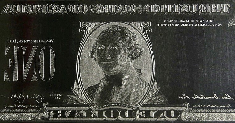 The reverse image of United States President George Washington is seen on an engraving plate for a US one dollar bill at the Bureau of Engraving and Printing in Washington November 14, 2014. The plate goes on the printing press which prints the currency. The dollar gave up strong early gains to turn lower on Friday after the battered euro turned higher on reports of short-covering in the common currency and a drop in U.S. bond yields. (Gary Cameron/Reuters)