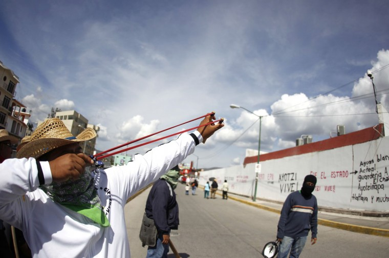 A member of the CETEG (State Coordinator of Education Workers of Guerrero) union uses a slingshot to shoot a stone towards a security camera as they block the entrance of the Attorney General's Office in Chilpancingo, in the Mexican state of Guerrero, November 24, 2014. The CETEG members blocked the access to the Attorney General's Office in Chilpancingo as part of a protest over the 43 missing trainee teachers. Embattled Mexican President Enrique Pena Nieto called on Mexico's states on Friday to swiftly adopt steps to modernise the justice system as he tries to defuse mass protests over the apparent massacre of 43 trainee teachers. Since the students were abducted by police and handed over to a local drug gang in the southwestern city of Iguala on September 26, a wave of discontent has hit the government, spurring calls at protests and on social media for Pena Nieto to step down. (REUTERS/Jorge Dan Lopez)