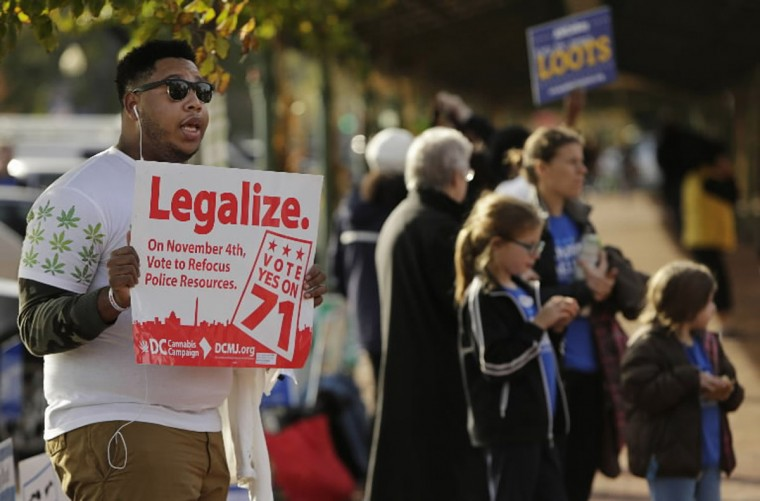Melvin Clay (L) of the DC Cannabis Campaign holds a sign urging voters to legalize marijuana, at the Eastern Market polling station in Washington November 4, 2014. Voters in the U.S. capital and two West Coast states will decide on Tuesday during national midterm elections whether to legalize marijuana in a test for broader cannabis legalization efforts across the United States. (Gary Cameron/Reuters)