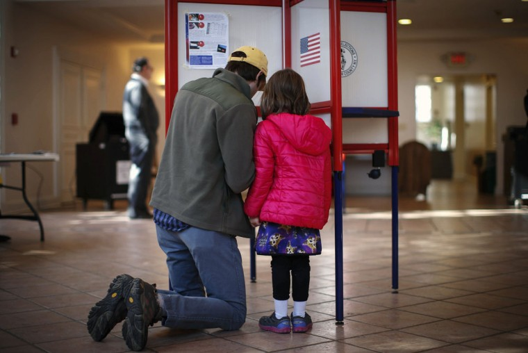 Kieran Campion kneels with his daughter Cordelia, 5, as he fills out his ballot to vote at the Presbyterian Church in the town of Mount Kisco, New York November 4, 2014. Americans were heading to the polls Tuesday in the midterm elections. (Mike Segar/Reuters)
