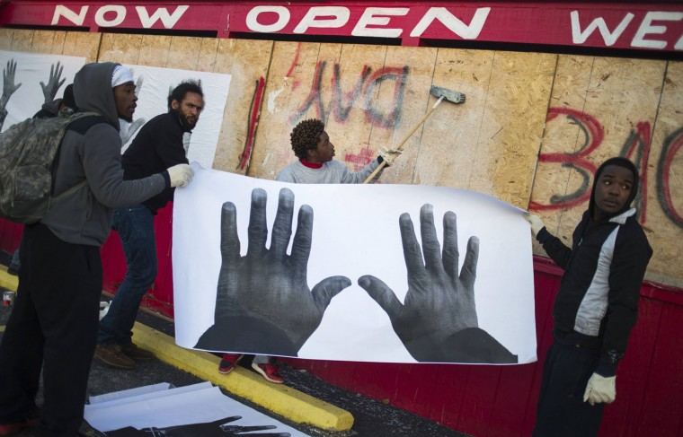 "Activist artists paste images, part of the #AllHandsOnDeck project by artist Damon Davis, on top of boarded-up businesses in Ferguson, Missouri November 20, 2014. The St. Louis suburb has been bracing for months to learn whether a St. Louis County grand jury will charge police officer Darren Wilson in the slaying of 18-year-old Michael Brown, a case that has become a flashpoint for often-troubled U.S. race relations. ""The aim of the project is to promote solidarity, hope and inspiration,"" Davis said. (Adrees Latif/Reuters)"
