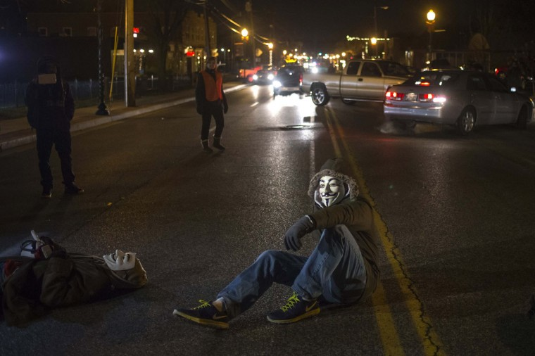 Activists, wearing Guy Fawkes masks, block traffic while protesting the shooting of Michael Brown, outside the Ferguson Police Station in Missouri, November 19, 2014. Residents of Ferguson prepared on Wednesday for a grand jury report expected soon on the fatal August shooting of Brown, an event that laid bare long-simmering racial tensions in the St. Louis suburb. (Adrees Latif/Reuters)