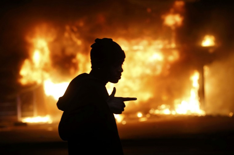 A man walks past a burning building during rioting after a grand jury returned no indictment in the shooting of Michael Brown in Ferguson, Missouri early November 25, 2014. Gunshots were heard and bottles were thrown as anger rippled through a crowd outside the Ferguson Police Department in suburban St. Louis after authorities on Monday announced that a grand jury voted not to indict a white officer in the August shooting death of an unarmed black teen. (REUTERS/Jim Young)