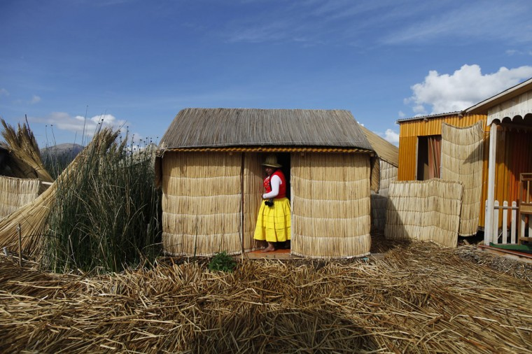 An Andean woman steps out of her house, a straw hut, in a Uros island at Lake Titicaca in Puno on November 5, 2014. (REUTERS/Enrique Castro-Mendivil)