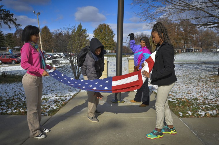 From left to right, students Daizha Jones, Kyle Turk, Aviauna Williams and Jayla Williams take down a flag as the school day ends at Riverview Gardens High School in St. Louis. Illustrates FERGUSON (category a), by Wesley Lowery © 2014, The Washington Post. Moved Thursday, Nov. 20, 2014. (Washington Post photo by Jahi Chikwendiu)