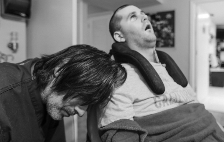 Ken rests his head on Ryan's arm after watching the WVU game together. (Kaitlin Newman/For The Baltimore Sun)