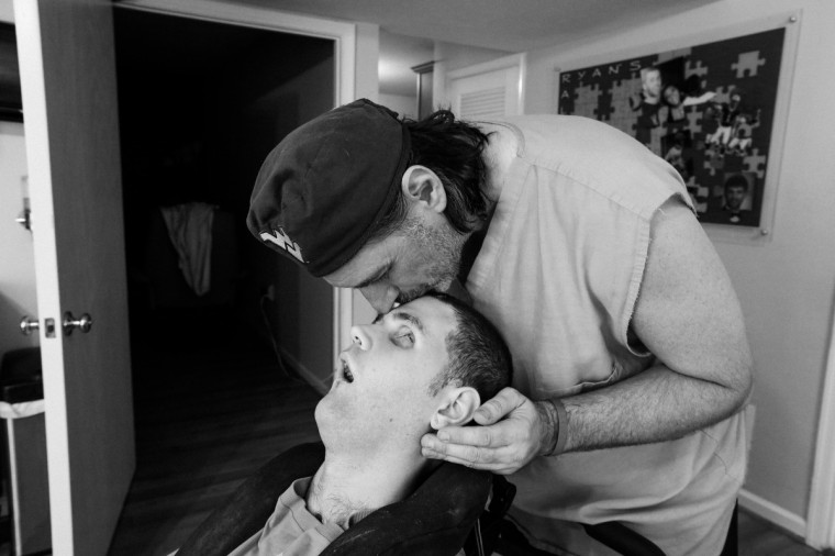 Ken kisses the top of Ryan's head during a break from physical therapy. (Kaitlin Newman/For The Baltimore Sun)