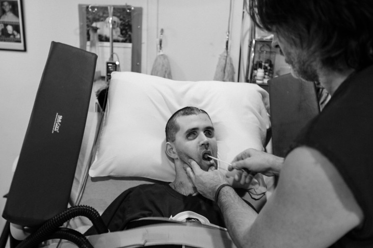 Ken cleans Ryan's mouth. Ryan eats through a feeding tube but it is still important to keep up with oral hygiene. (Kaitlin Newman/For The Baltimore Sun)