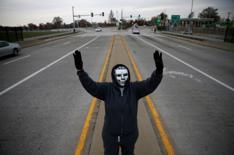 "Demonstrators yell ""Hands Up, Don't Shoot"" alongside a highway overpass to voice their opinions as the area awaits a grand jury decision on November 15, 2014 near Ferguson, Missouri. The area around St Louis, Missouri prepares for the grand jury decision in the shooting death of Michael Brown by Darren Wilson, a Ferguson police officer. (Photo by Joe Raedle/Getty Images)"