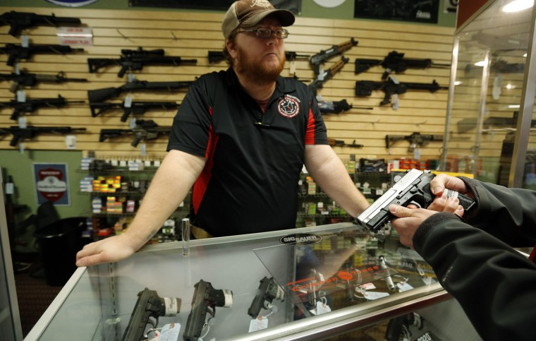 Metro Shooting Supplies' employee Chris Cox speaks to a customer about the purchase of a 9mm handgun in Bridgeton, Missouri, November 13, 2014. The store has reported an increase in gun sales as the area waits for a grand jury to reach a decision this month on whether to indict Darren Wilson, the white police officer who shot and killed the 18-year-old Mike Brown, who was black, on Aug. 9 in the St. Louis suburb of Ferguson. (Jim Young/Reuters)