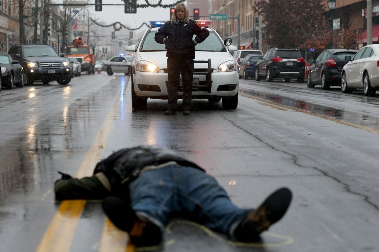 A Washington University in St Louis police officer looks on as a demonstrator lays on the ground during a mock death protest of the shooting death of Michael Brown by a Ferguson police officer on November 16, 2014 in St. Louis, Missouri. The area around St Louis, Missouri prepares for the grand jury decision in the shooting death of Michael Brown by Darren Wilson, a Ferguson police officer. (Photo by Joe Raedle/Getty Images)
