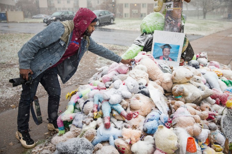 Aaron Jeremiah, of Houston, leaves a memento at a memorial near the location where 18-year-old Michael Brown was shot on November 16, 2014 in Ferguson, Missouri. Brown was killed by Darren Wilson, a Ferguson police officer, on August 9. Residents in the area are on edge as they wait to hear if the grand jury will vote to indict Wilson for the shooting. The decision is expected sometime in November. (Photo by Scott Olson/Getty Images)