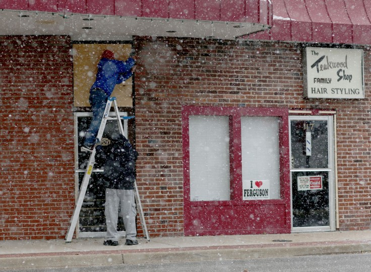Tony (L) and Tim, who didn't want to provide their last names, place plywood over a window as they prepare to try to protect a business from any violent reaction to the grand jury decision on November 17, 2014 in Ferguson, Missouri. The area around St Louis, Missouri prepares for the release of the grand jury decision in the shooting death of Michael Brown by Darren Wilson, a Ferguson police officer. (Photo by Joe Raedle/Getty Images)